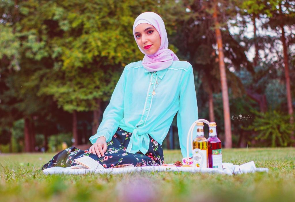 صورة فتاة تجلس على بساط في الحديقة