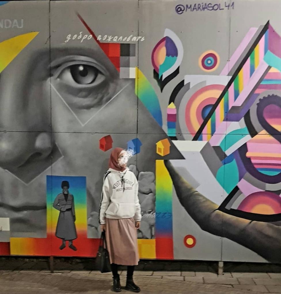 صورة لرسم تشكيلي على حائط تقف أمامه فتاة